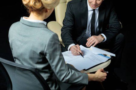 Photo pour Businessman and businesswoman sitting on chairs and signing papers isolated on black - image libre de droit