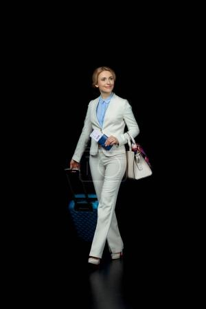 Photo for Happy blonde businesswoman with suitcase in white suit ready to trip  isolated on black - Royalty Free Image