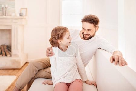 Cute little girl with father sitting together on sofa and smiling each other