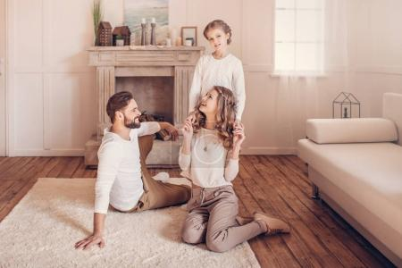 Happy young family with one child spending time together at home
