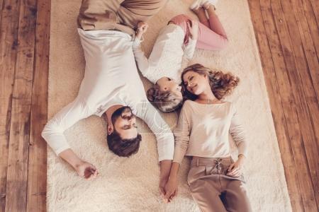 Draufsicht auf glückliche Familie mit einem Kind, das zusammen auf Teppich liegt