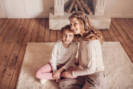 Photo for High angle view of happy mother and daughter sitting together on carpet and looking away - Royalty Free Image
