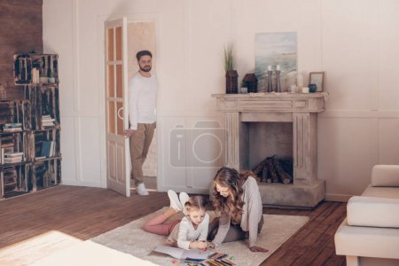 Man standing in doorway and looking at mother with daughter drawing on floor