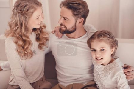 Happy young family with one child sitting embracing together at home