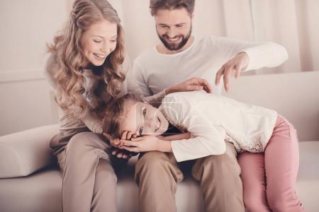 Foto de Hija feliz tumbado en el regazo de los padres y mirando a cámara - Imagen libre de derechos