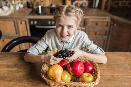 Foto de Adorable niña con frutas diferentes, sentado a la mesa en la cocina - Imagen libre de derechos