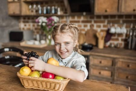 adorable girl with different fruits sitting at table in kitchen