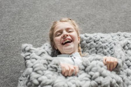 Photo pour Adorable fille riant et couché sur le sol avec couverture en tricot gris - image libre de droit