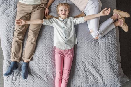 Happy adorable daughter with mother and father relaxing on bed at home