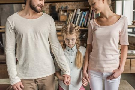 Cropped shot of young family with one child standing together and holding hands