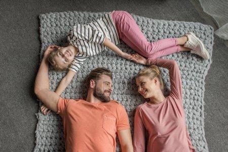 Photo pour Vue de dessus d'une famille heureuse avec un enfant couché ensemble sur tapis tricoté gris - image libre de droit