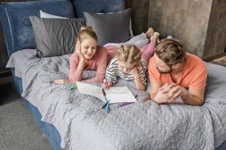 Photo pour Parents heureux couchés sur le lit et regardant la fille souriante dessin - image libre de droit