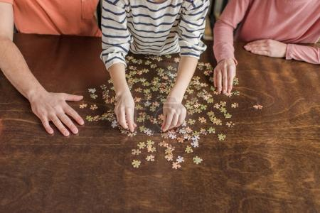 Close-up partial view of family with one child playing with puzzles on table