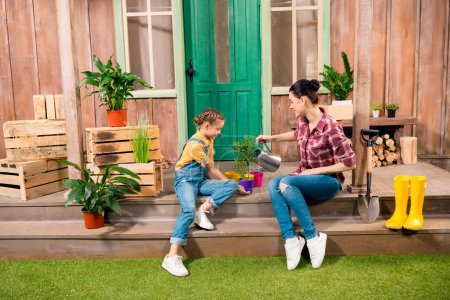 Happy mother and daughter sitting on porch and watering plant