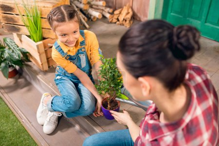 High angle view of mother and smiling daughter sitting on porch and watering plant