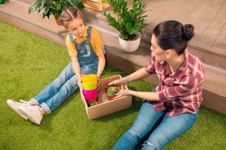 High angle view of beautiful mother and daughter sitting on lawn with pots and potted plants