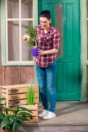 Photo pour Jeune femme brune souriante debout sur le porche avec plante verte en pot - image libre de droit
