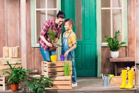 Foto de Sonriente madre e hija quitando la planta y hablando en el porche - Imagen libre de derechos