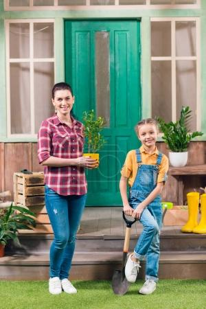 Smiling mother with potted plant and daughter with garden shovel looking at camera