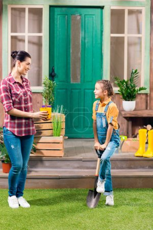 Smiling mother with potted plant and daughter with garden shovel looking at each other