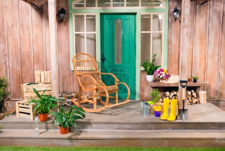 Potted plants and rocking chair on porch with gardening tools