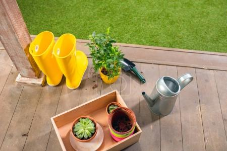 watering can, yellow boots and plants in wooden box on porch