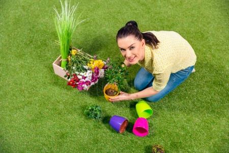 attractive gardener with plants and flowerpots sitting on green grass