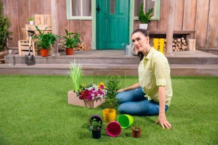 Photo pour Jardinier attrayant avec des plantes et des pots de fleurs assis sur l'herbe verte - image libre de droit