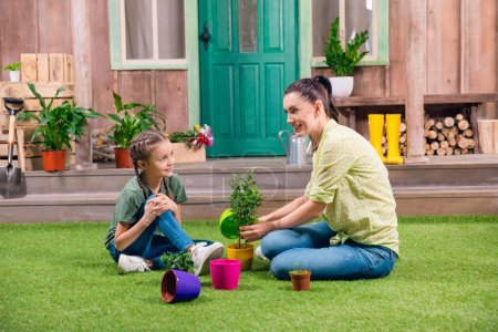 Photo for Mother and daughter with plants and flowerpots sitting on green grass - Royalty Free Image
