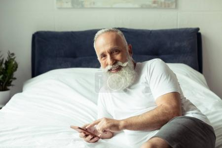 Photo for Bearded senior man using smartphone while lying on bed - Royalty Free Image