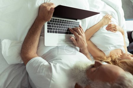Mature couple in bed with laptop
