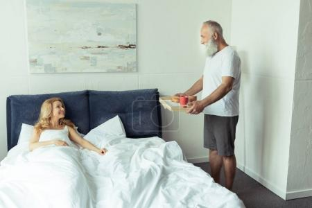 Mature couple with breakfast in bed