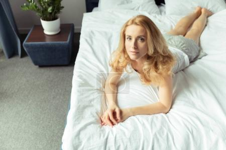 Photo for Portrait of pensive blond woman lying on bed at home - Royalty Free Image