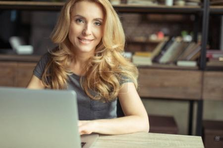 Photo for Portrait of smiling woman working on laptop at home office workplace - Royalty Free Image
