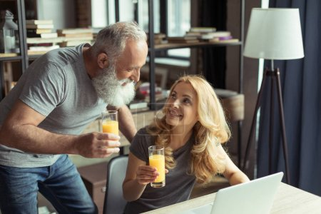 Photo for Casual middle aged couple drinking orange juice at home - Royalty Free Image