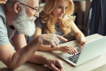 Photo for Casual middle aged couple working on laptop together - Royalty Free Image