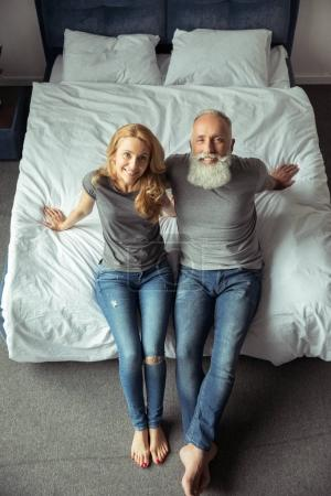 middle aged couple sitting on bed