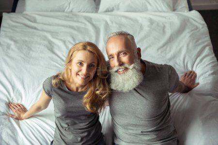 Photo for Casual middle aged couple sitting on bed and smiling - Royalty Free Image