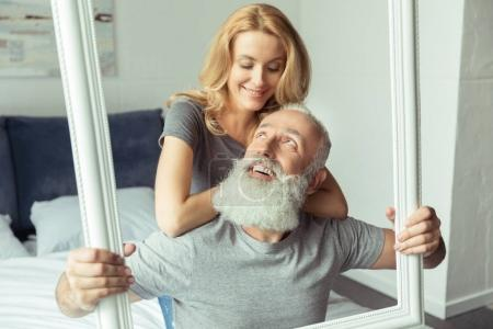 Photo for Casual middle aged couple sitting on bed with picture frame - Royalty Free Image