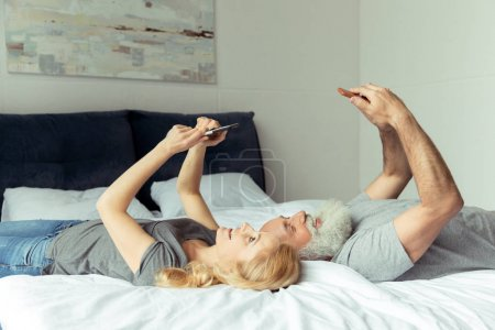 Photo for Casual middle aged couple lying in bed with smartphones - Royalty Free Image