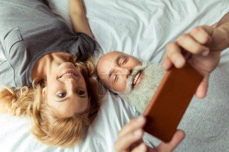 Foto de Par de medio casual acostado en la cama y tomar selfie - Imagen libre de derechos