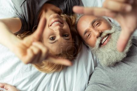 Photo for Casual middle aged couple lying in bed and smiling - Royalty Free Image