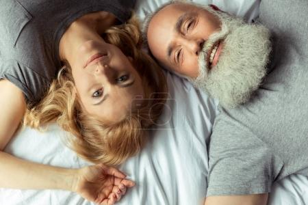 middle aged couple lying in bed