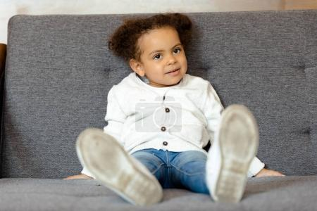 Photo for Adorable little african american girl sitting on sofa at home - Royalty Free Image