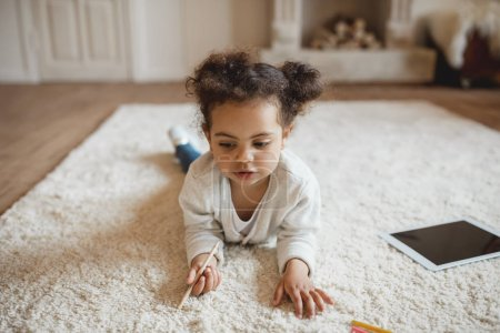 Photo for Adorable little african american girl drawing with pencils and lying on carpet at home - Royalty Free Image