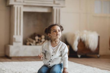 Foto de Adorable niña afroamericana sentada en alfombra en casa - Imagen libre de derechos