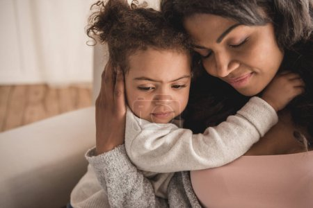 Photo for Close-up portrait of beautiful african american mother and daughter hugging at home - Royalty Free Image