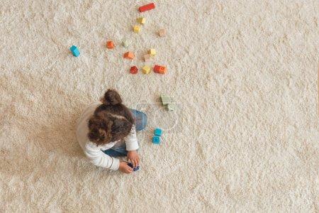 Photo pour Vue aérienne de la petite fille jouant avec des cubes à la maison - image libre de droit