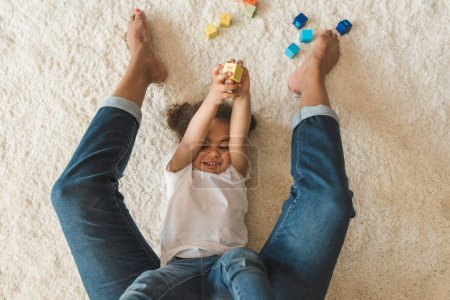 Kid girl playing with mother on carpet