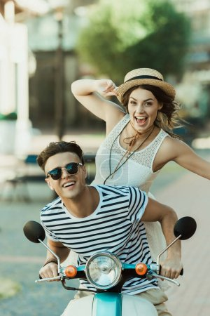 Photo for Excited young stylish couple having fun and riding scooter in city - Royalty Free Image
